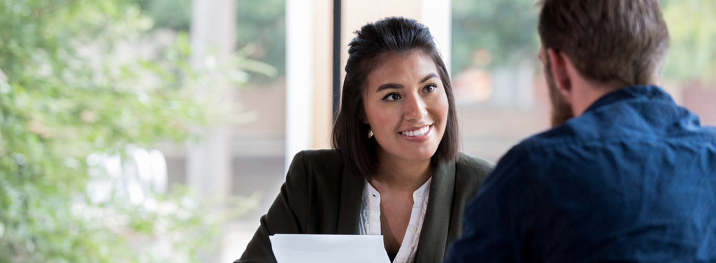 Woman facing man in business professional setting